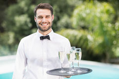Smiling waiter carrying champagne flutes on tray. Portrait of smiling waiter carrying champagne flutes on tray at poolside Stock Images