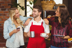 Smiling waiter and customers discussing. At the coffee shop Stock Images