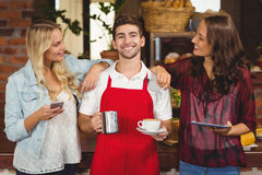 Smiling waiter and customers looking at the camera. Portrait of a smiling waiter and customers at the coffee shop Royalty Free Stock Photo