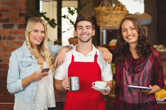 Smiling waiter and customers looking at the camera. Portrait of a smiling waiter and customers at the coffee shop Royalty Free Stock Images
