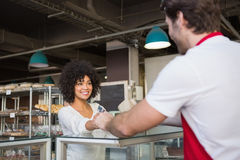 Smiling waiter doing transaction with customer. At the bakery Stock Images