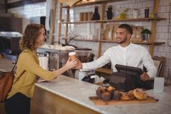 Smiling waiter giving disposable coffee cup to young female customer at counter. In cafeteria Royalty Free Stock Photo