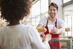 Smiling waiter giving lunch and hot drink to customer. At the bakery Royalty Free Stock Photo