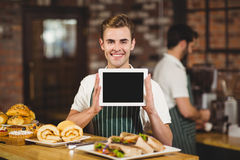 Smiling waiter holding a digital tablet. Portrait of a waiter holding a digital tablet at the coffee shop Stock Photo