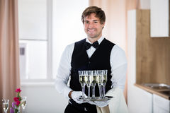 Smiling Waiter Holding Tray Of Champagne. Portrait Of A Smiling Waiter Holding Tray Of Champagne Royalty Free Stock Image
