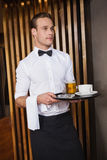 Smiling waiter holding tray with coffee cup and pint of beer. In a bar royalty free stock photo