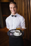 Smiling waiter holding tray with coffee cup and pint of beer. In a bar stock images