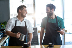 Smiling waiter interacting while making cup of coffee at counter Royalty Free Stock Images