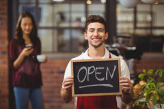 Smiling waiter posing with a chalkboard open sign Royalty Free Stock Photos