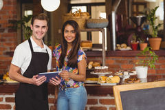 Smiling waiter and pretty customer looking on tablet stock photos