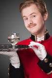 Smiling Waiter in red uniform. With a tray with glasses on a grey background Stock Images