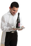 Smiling waiter, servant or bartender. A smiling waiter, bartender, servant or attendant carrying a wine bottle and glasses.  White background Stock Photos