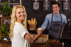 Smiling waiter serving a coffee to a customer. At the cafe Stock Images