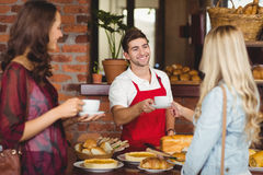 Smiling waiter serving a coffee to a customer Royalty Free Stock Photo