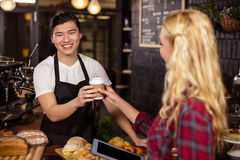 Smiling waiter serving a coffee to a customer Stock Photos