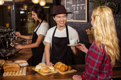 Smiling waiter serving a coffee to a customer Royalty Free Stock Photography