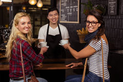 Smiling waiter serving a coffee to customers Royalty Free Stock Image