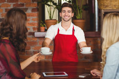 Smiling waiter serving coffees to customers. Portrait of a waiter serving coffees to customers at the coffee shop Stock Images