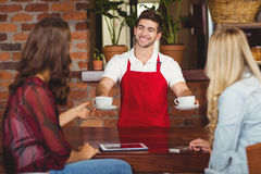 Smiling waiter serving coffees to customers. Waiter serving coffees to two customers at the coffee shop Stock Image