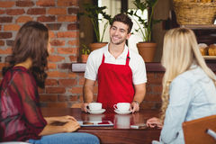 Smiling waiter serving coffees to customers. Waiter serving coffees to two customers at the coffee shop Stock Images