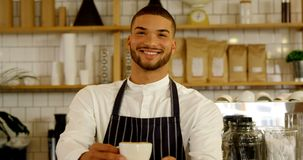 Smiling waiter serving cup of coffee 4k