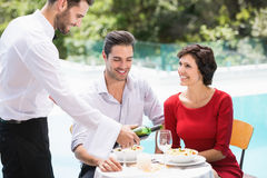Smiling waiter serving red wine to couple Stock Photography