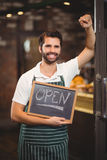 Smiling waiter showing chalkboard with open sign Stock Photos