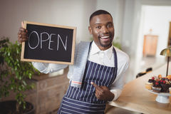 Smiling waiter showing chalkboard with open sign Royalty Free Stock Photos