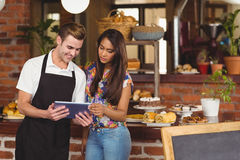 Smiling waiter showing pretty customer tablet Stock Photo