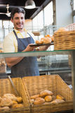 Smiling waiter showing tray of breads Stock Photos