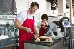 Smiling waiter slicing cake with waitress behind him. At the bakery Stock Photo