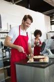 Smiling waiter slicing cake with waitress behind him Stock Image