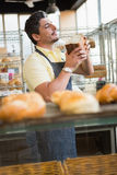 Smiling waiter smelling bread freshly baked Royalty Free Stock Photography