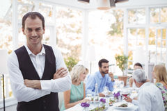 Smiling waiter standing with arms crossed while friends dining in background. Portrait of smiling waiter standing with arms crossed while friends dining in Stock Image