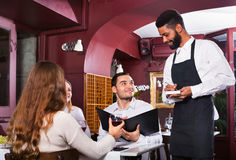 Smiling waiter taking care of adults. At cafe table Royalty Free Stock Images