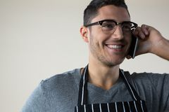 Smiling waiter talking on the mobile phone Royalty Free Stock Image