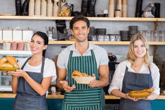 Smiling waiter and two waitresses holding plate of bread rolls Stock Photos