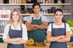 Smiling waiter and two waitresses standing with arms crossed. In cafe Royalty Free Stock Photos