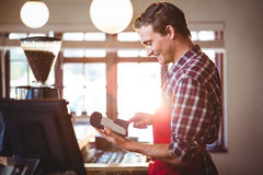 Smiling waiter using credit card machine Stock Images