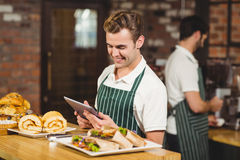 Smiling waiter using a digital tablet Stock Images