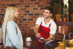 Smiling waiter using the pin terminal royalty free stock photography
