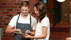 Smiling waiter using tablet with a customer. At the coffee shop stock footage