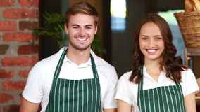 Smiling waiter and waitress gesturing thumbs up. Portrait of a waiter and waitress gesturing thumbs up at the coffee shop stock video