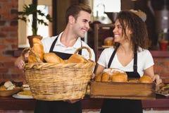 Smiling waiter and waitress holding basket full of bread rolls Stock Image