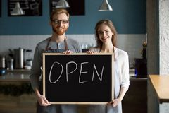 Smiling waiter and waitress holding chalkboard with open sign, p royalty free stock images