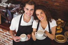 Smiling waiter and waitress holding cup of coffee Royalty Free Stock Photos