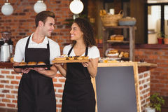 Smiling waiter and waitress holding tray with muffins Stock Images