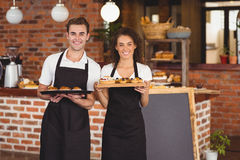 Smiling waiter and waitress holding tray with muffins Stock Image