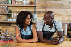 Smiling waiter and waitress interacting with each other at counter. In caf Stock Photo