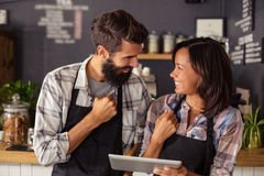 Smiling waiter and waitress interacting while using digital tablet Royalty Free Stock Image